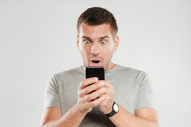 Shocked man chatting by mobile phone. Free Photo