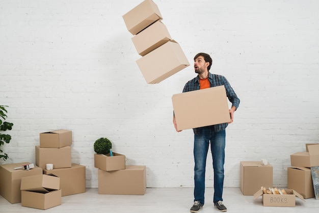 Shocked man looking at the fallen moving cardboard boxes Free Photo