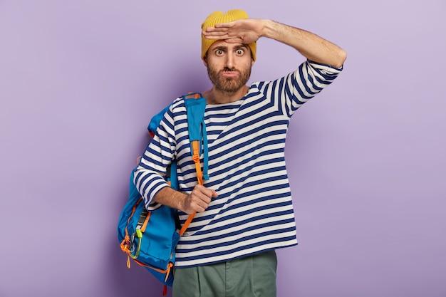 ショックを受けた男の旅行者は目を飛び出し、遠くに何か奇妙なものを見て、バックパックを運ぶ 無料写真