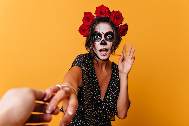 黄色の背景にポーズをとってショックを受けたメキシコのゾンビ。驚きを表現するハロウィーンの衣装でインスピレーションを得た女性モデル。 無料写真