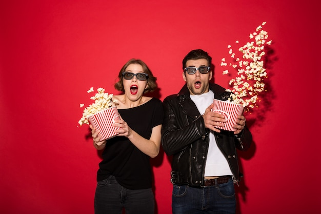 Shocked punk couple scatter popcorn and looking Free Photo