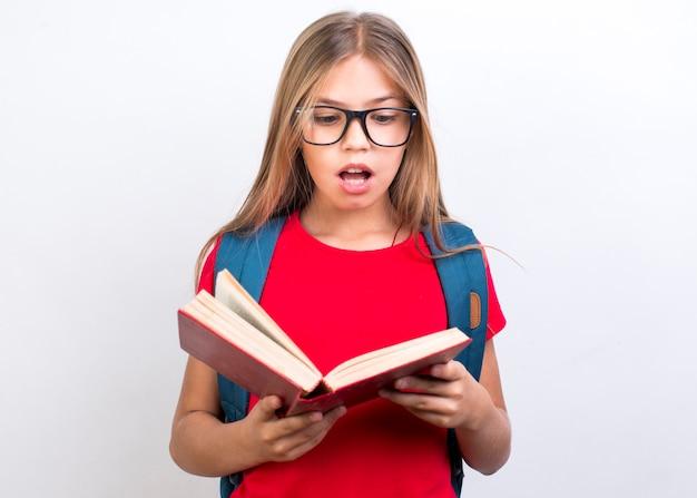 Shocked schoolgirl with book Free Photo