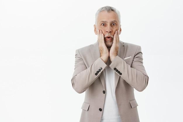 Шокированный старший мужчина в костюме выглядит изумленным, задыхаясь от удивления Бесплатные Фотографии