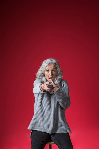 Shocked senior woman changing the channel with remote control against red backdrop Free Photo