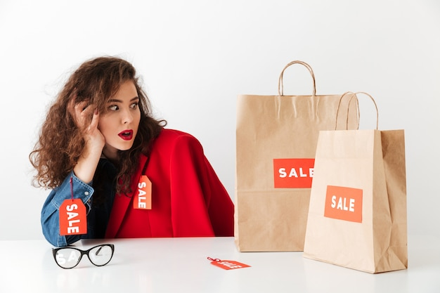 Shocked shopping sale woman sitting with paper shopping bags Free Photo