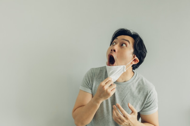 Shocked and surprised face of man wearing white hygienic mask in grey t-shirt. Premium Photo