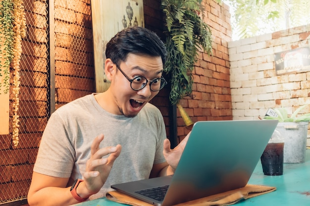 Shocked and surprised face of man works on his laptop in the cafe. Premium Photo