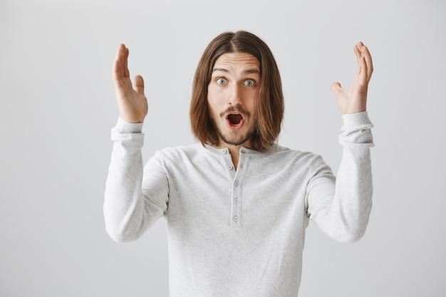 Uomo sorpreso scioccato che alza le mani in alto, trionfante eccitato Foto Gratuite