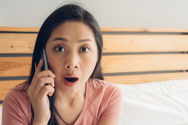 Shocked and surprised woman is having a phone conversation on her bed. Premium Photo