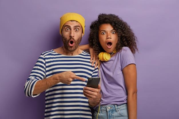 Шокированные, напуганные женщины и мужчины смешанной расы читают смс электронной почты на смартфоне, получают ужасающие новости, Бесплатные Фотографии