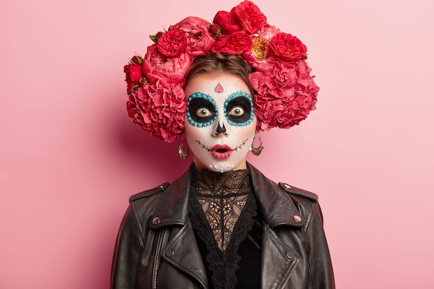 Shocked terrified young woman has scary ghost face, wears artistic makeup for day of dead holiday, wears black leather jacket, models over rosy studio background. skull female symbolizing death Free Photo