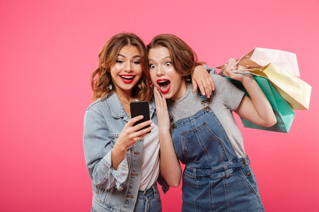 Shocked two women friends holding shopping bags using mobile phone. Free Photo
