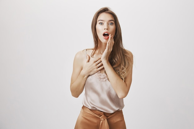 Shocked woman gasping, touch cheek and stare camera Free Photo