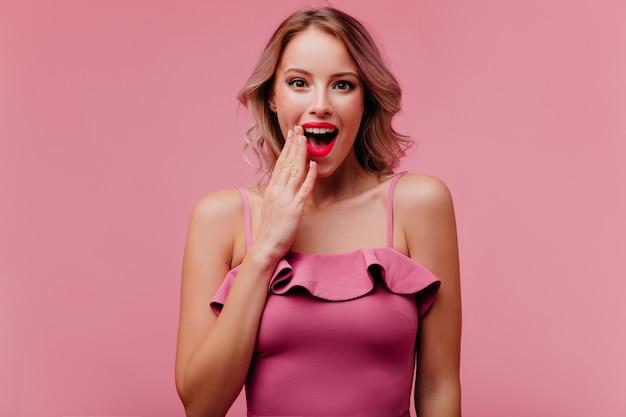 Шокированная женщина в хорошем настроении с красивым макияжем и яркими губами позирует перед камерой, демонстрируя удивление Бесплатные Фотографии