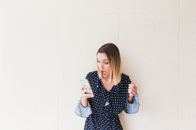 Shocked woman looking at mobile phone Free Photo