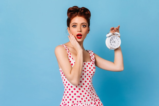 Shocked woman in polka-dot dress holding clock. amazed ginger pinup lady showing time on blue space. Free Photo