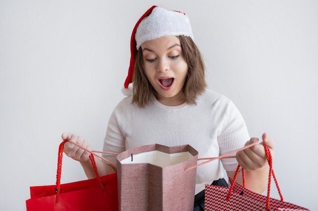 Shocked woman in santa hat opening bag with christmas present Free Photo