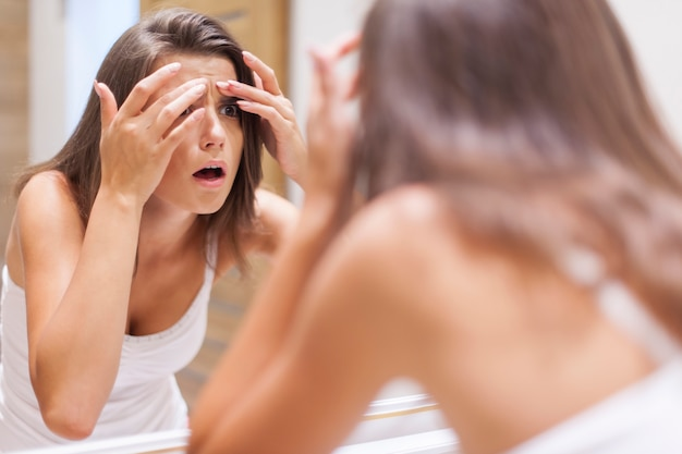 Shocked woman squeezing pimple in bathroom Free Photo