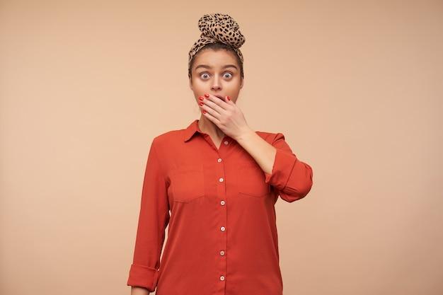 Scioccato giovane donna dai capelli castani che copre la bocca con il palmo sollevato mentre guarda con stupore davanti con gli occhi spalancati, isolato sopra il muro beige Foto Gratuite