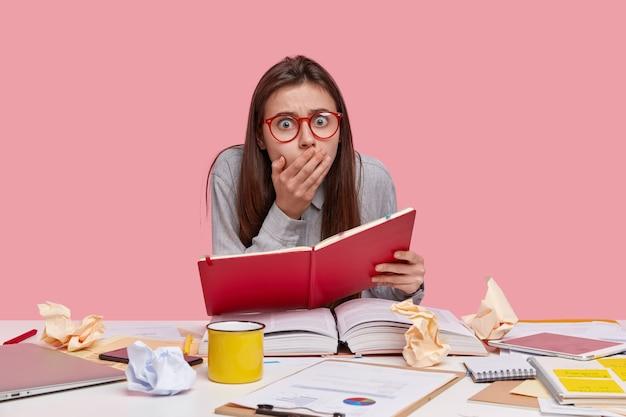ショックを受けた若い大学生は、厚い開いた本、ラップトップコンピューターに囲まれた赤い日記を持っており、締め切りのタスクがあることに驚いて、コーヒーを飲みます 無料写真