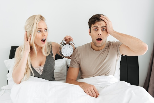 Shocked young couple sitting in bed with opened mouth and holding alarm clock Free Photo
