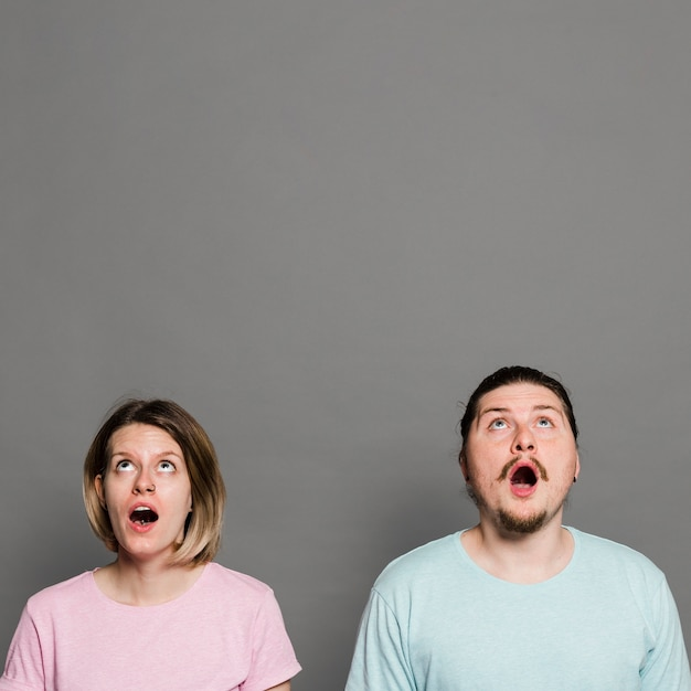 Shocked young couple with their mouth opened looking up against grey wall Free Photo