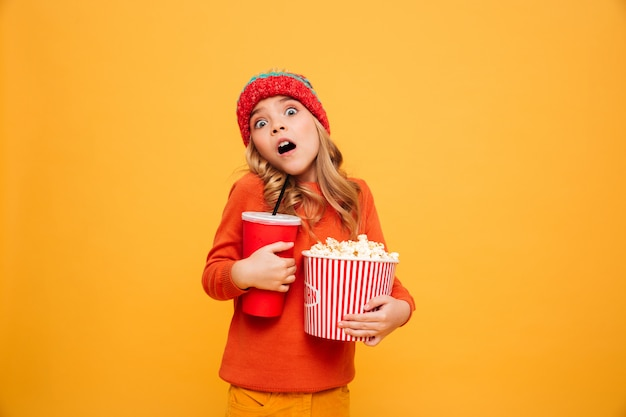 Shocked young girl in sweater and hat holding popcorn and plastic cup while looking at the camera over orange Free Photo