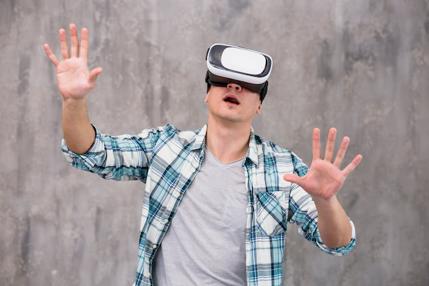 Shocked young guy in vr helmet Free Photo