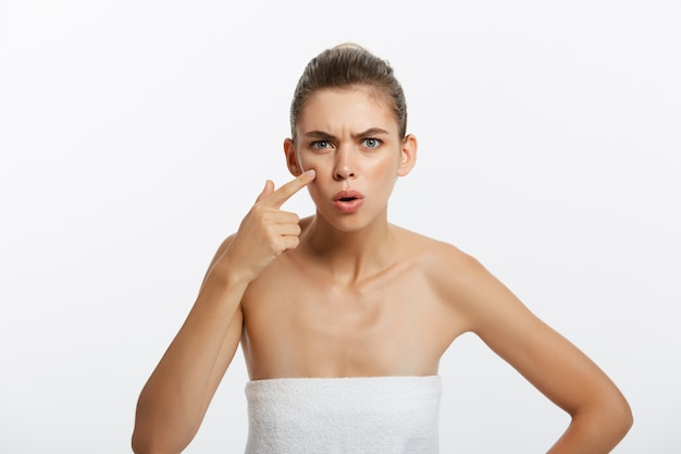 Shocked young half naked woman examining her face while looking at the mirror Premium Photo