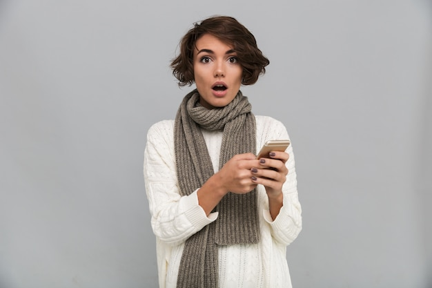 Shocked young lady wearing scarf chatting by mobile phone. Free Photo