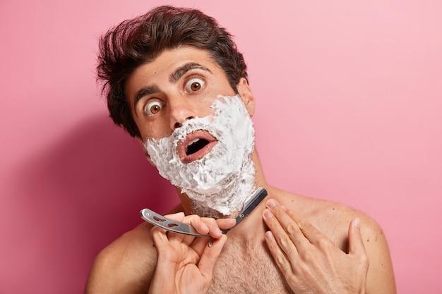 ショックを受けた若い男は、泡を塗り、あごひげを整える準備をし、かみそりの刃を持って、毎日のひげそりに飽き飽きしています。 無料写真