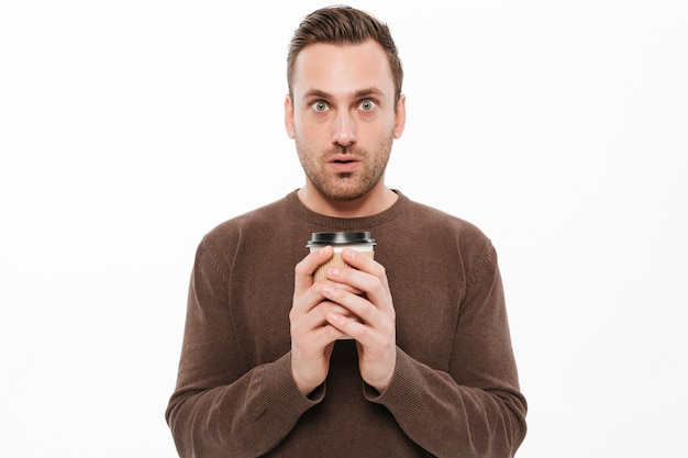 Shocked young man drinking coffee. Free Photo