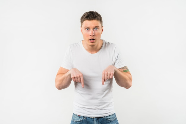 Shocked young man pointing her fingers downward against white backdrop Free Photo