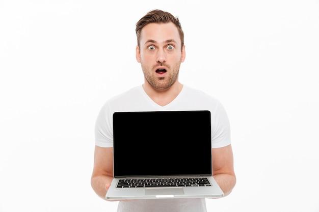 Shocked young man showing display of laptop. Free Photo