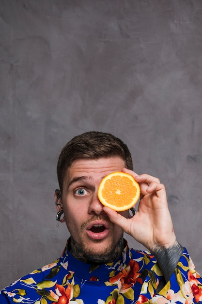 Shocked young man with pierced ears and nose holding and orange slice in front of eyes against grey wall Free Photo