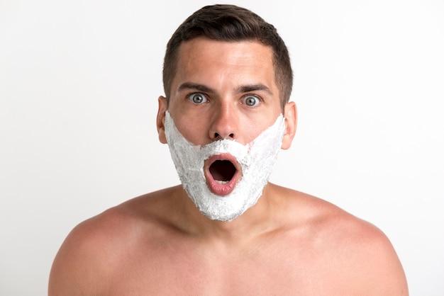 Shocked young shirtless man applied shaving cream looking at camera Free Photo