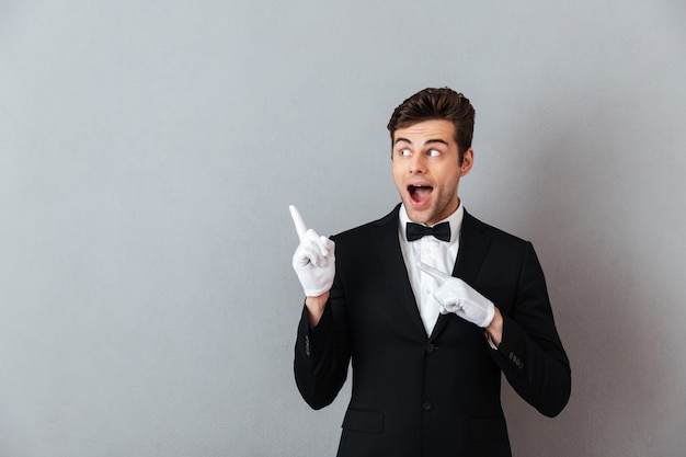 Shocked young waiter pointing. Free Photo