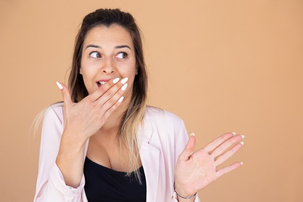 Shocked young woman covering mouth with hand Free Photo