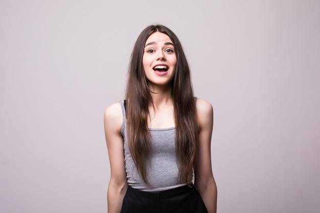 Giovane donna scioccata che guarda con la bocca aperta. isolato su grigio Foto Gratuite