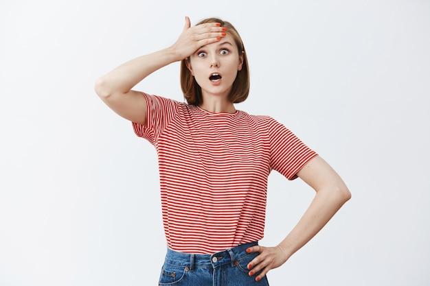 La giovane donna scioccata dà un pugno alla fronte e sussulta spaventata Foto Gratuite