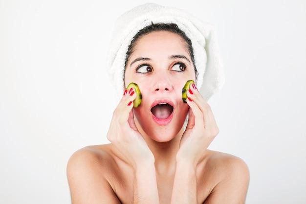 Shocked молодая женщина обмена сообщениями с огуречным ломтиком на белом фоне Бесплатные Фотографии