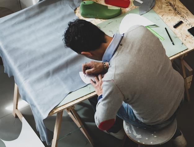 Shoe designer working with leather. Premium Photo