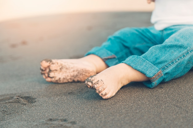 Shoeless feet of baby sitting on sand Free Photo