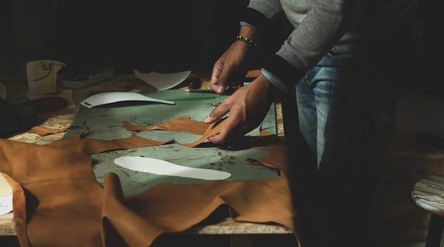 Shoemaker cutting leather Premium Photo