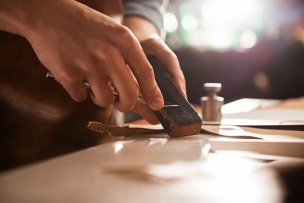 Shoemaker sharpening a knife Free Photo