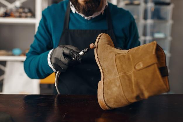 靴屋は靴底を研ぎ、靴の修理をします Premium写真