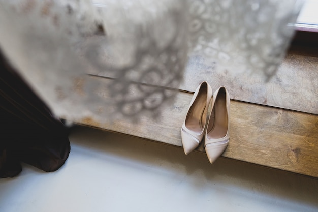Shoes of the bride on background of wedding veils. Premium Photo