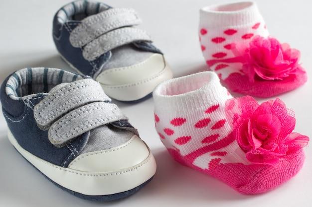 어린 소년을위한 신발과 소녀를위한 분홍색 양말. 흰 바탕 프리미엄 사진