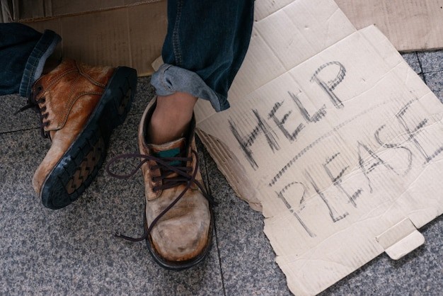 Shoes of homeless people with cardboard text Premium Photo