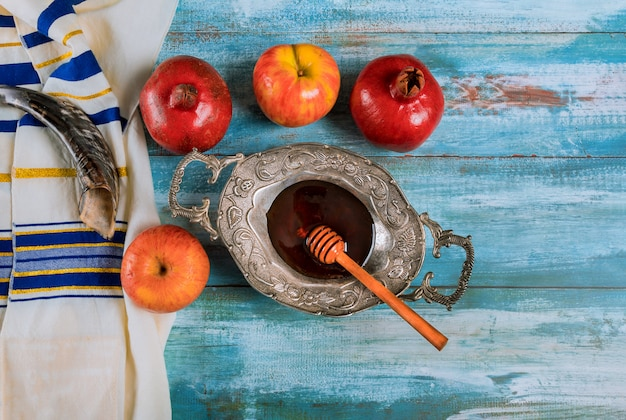 Shofar and tallit with glass honey and fresh ripe apples. jewish new year symbols. rosh hashanah Premium Photo